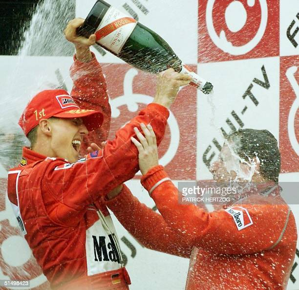 German Ferrari driver Michael Schumacher sprays champagne on his teammanager Jean Todt of France on the podium 08 October 2000 of the Suzuka...