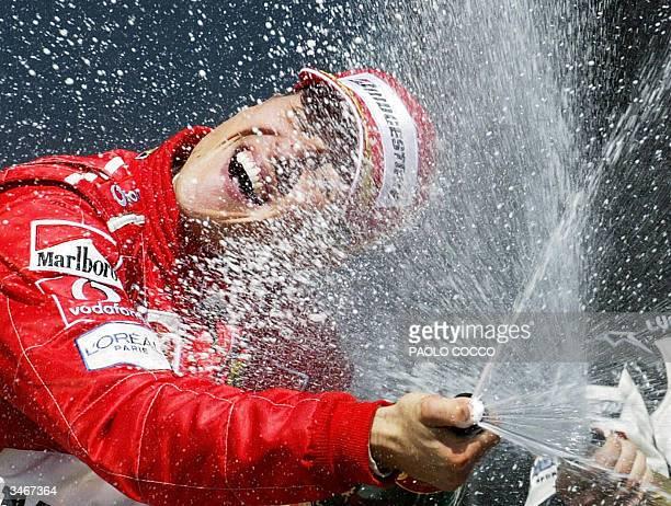 German Ferrari driver Michael Schumacher sprays champagne on the podium of the Imola racetrack after the San Marino Grand Prix 25 April 2004 in Imola...