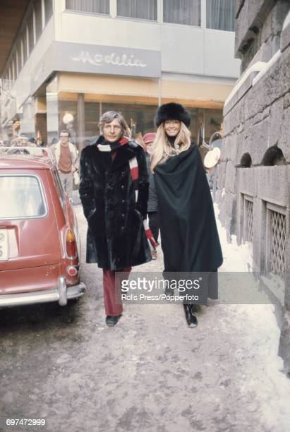 German film maker photographer and socialite Gunter Sachs pictured with his wife Swedish model Mirja Larsson as they walk down a snow covered street...