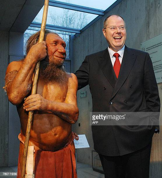 German Finance minister Peer Steinbrueck laughs as he poses next to a reconstruction of a Neanderthal Man as he visits the Neanderthalmuseum in...