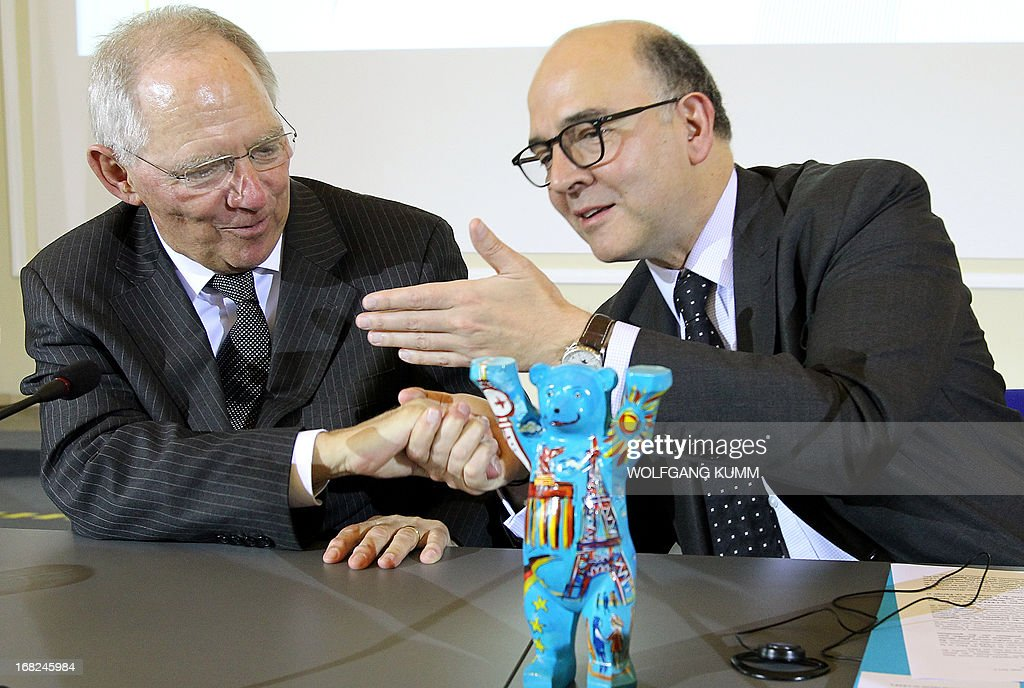 German Finance Minister Wolfgang Schaeuble (L) and French Finance Minister Pierre Moscovici shake hands as they address a press conference at the finance ministry in Berlin on May 7, 2013, on the occasion of the 25th anniversary of the Franco-German Economic and Financial Council.