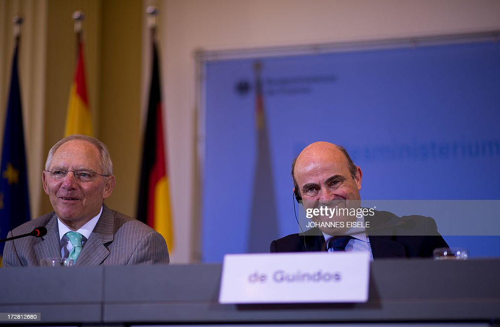 German Finance Minister Wolfgang Schaeuble (L) and his Spanish counterpart Luis de Guindos address a press conference after signing an agreement outlining financial support to Spanish small and medium-sized businesses in Berlin on July 4, 2013. Germany and Spain signed an agreement to boost access to affordable credit for small and medium enterprises in the recession-hit southern European country in a bid to foster growth and create jobs. AFP PHOTO / JOHANNES EISELE