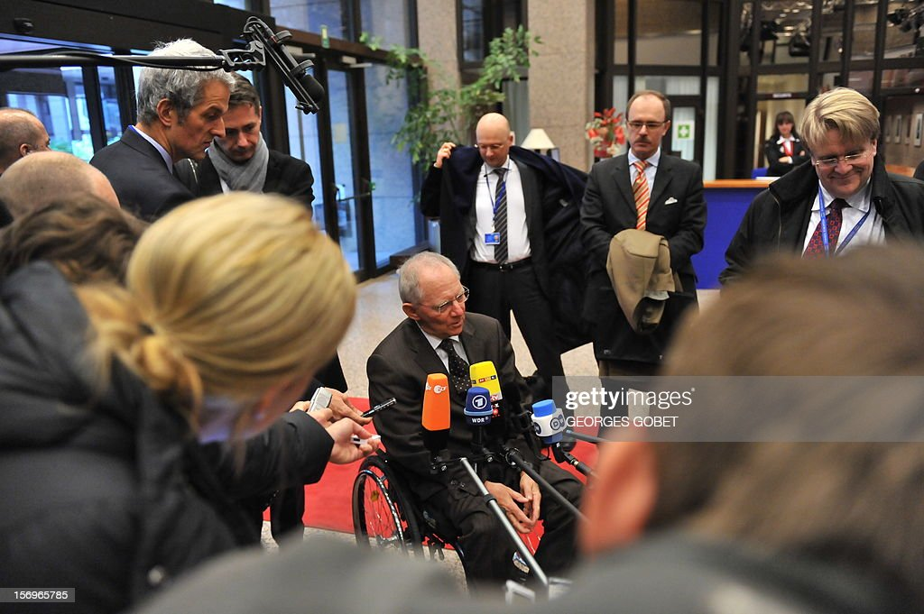 German Finance Minister, Wolfgang Schaeuble (C) answers the media upon his arrival on November 26, 2012 prior to an Eurozone meeting at the EU Headquarters in Brussels. Eurozone finance ministers and other creditors of Greece as IMF and ECB meet for the third time in two weeks on immediate funding to avert a threat of bankruptcy for Greece and to deal with the country's ever-growing mountain of debt.