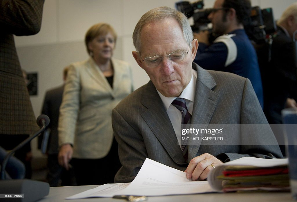 German Finance Minister Wolfgang Schaeuble browses documents as Chancellor Angela Merkel arrives for a meeting with their conservative CDU party's parliamentary group on May 20, 2010 in Berlin. Merkel said during a conference on financial regulation she would lead a campaign for a tax on financial markets at the next summit of the Group of 20 major economies in June and called for international support.