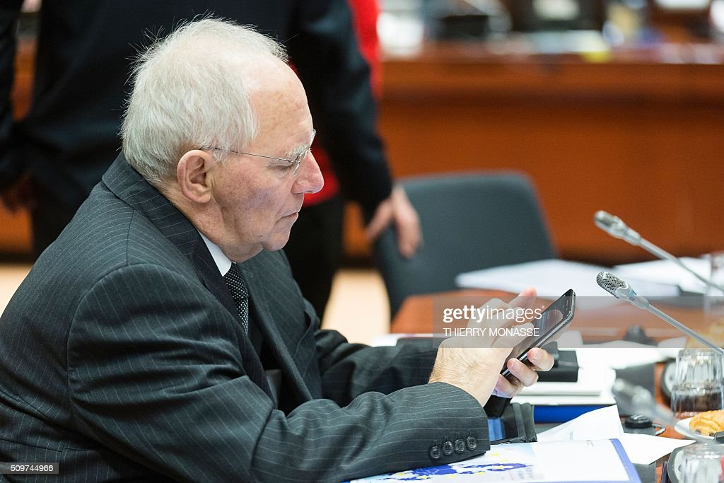 German Finance Minister Wolfgang Schaeuble checks his mobile phone prior to the start of the European Union Eco-Finance Council meeting at the EU Council building in Brussels on February 12, 2016. AFP PHOTO / THIERRY MONASSE / AFP / THIERRY MONASSE