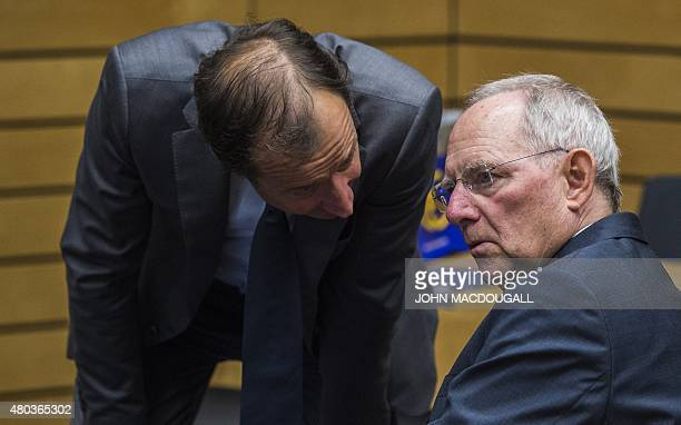 German Finance Minister Wolfgang Schaeuble confers with an unidentified official at the beginning of a meeting of the Eurogroup finance ministers in...