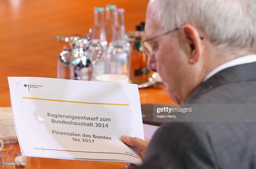 German Finance Minister Wolfgang Schaeuble holds a draft proposal of an outline of the country's 2014 federal budget as he arrives for the weekly German federal Cabinet meeting on June 26, 2013 in Berlin, Germany. The budget was high on the morning's agenda for discussion at the meeting.