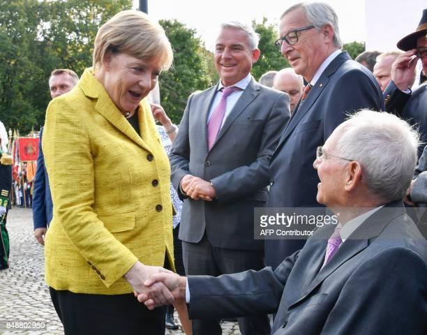 German Finance Minister Wolfgang Schaeuble is congratulated by German Chancellor Angela Merkel as European Commission President JeanClaude Juncker...