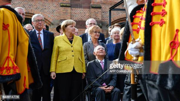 German Finance Minister Wolfgang Schaeuble poses with his guests European Commission President JeanClaude Juncker and German Chancelor Angela Merkel...