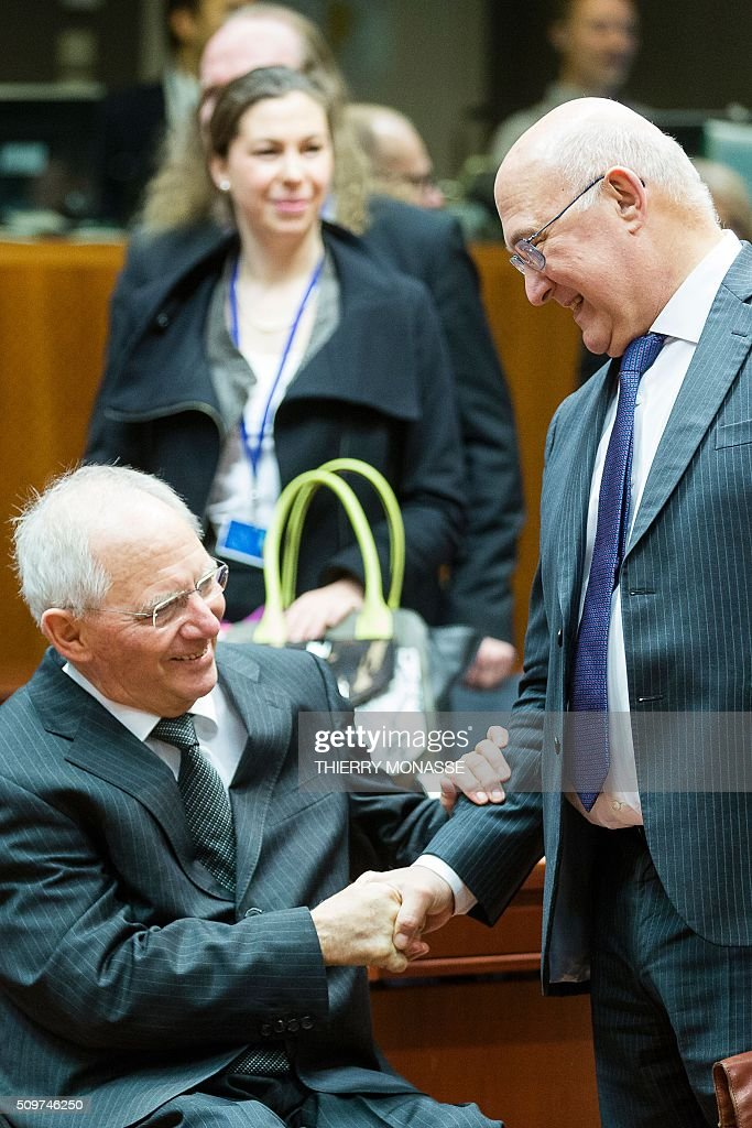 German Finance Minister Wolfgang Schaeuble (L) shakes hand with his French counterpart Michel Sapin prior to the start of the European Union Eco-Finance Council meeting at the EU Council building in Brussels on February 12, 2016. AFP PHOTO / THIERRY MONASSE / AFP / THIERRY MONASSE