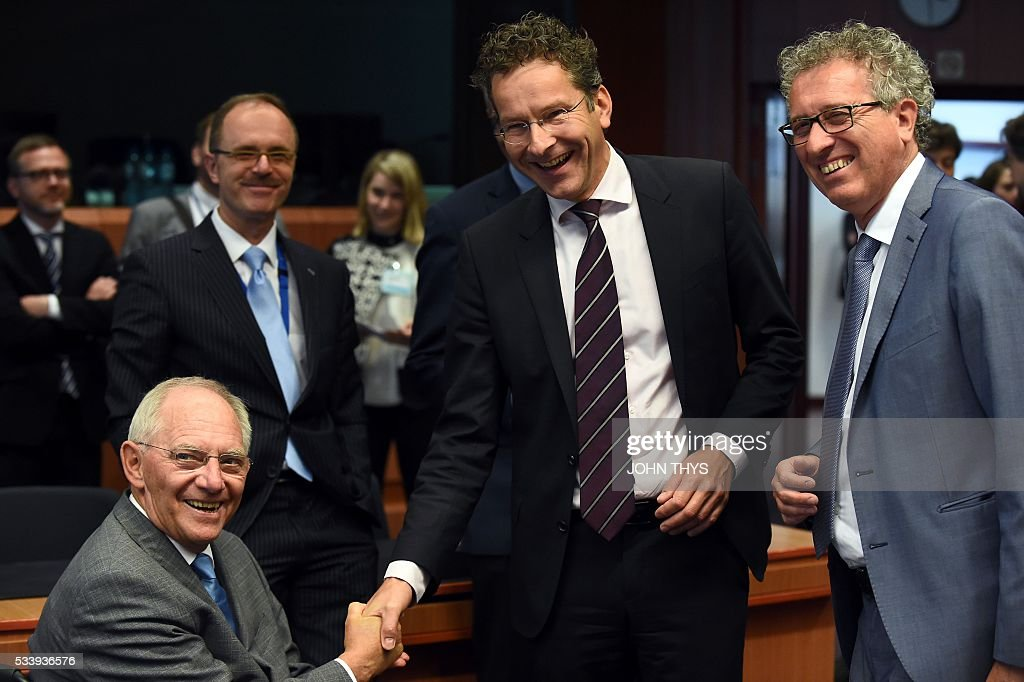 German Finance Minister Wolfgang Schaeuble shakes hands with Dutch Finance Minister and president of Eurogroup Jeroen Dijsselbloem next to Luxembourg's Finance Minister Pierre Gramegna during a Eurogroup meeting at the European Union headquarters in Brussels on May 24, 2016. Eurozone finance ministers said they hoped to unlock vital bailout cash for Greece on May 24, but warned of tough talks on debt relief that the IMF has demanded as the price for staying with the programme. / AFP / JOHN