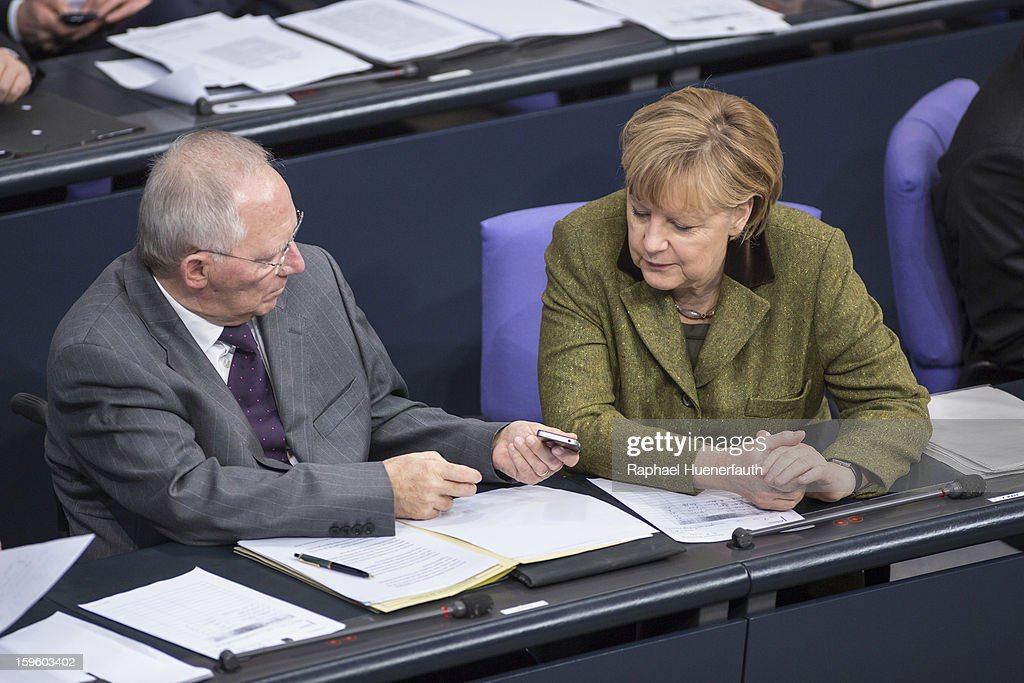 German Finance Minister Wolfgang Schaeuble (L) shows German Chancellor Angela Merkel (R) his phone screen during the Annual Economic Report 2013 of the Federal Government at Reichstag, the seat of the German Parliament (Bundestag), on January 17, 2013 in Berlin, Germany. German Economics Minister Philipp Roesler warned that a short-term deal with the euro crisis through inflation, stating that it's not 'A price we are not willing to pay - the price of monetary stability' in his inaugural speech to the annual economic report in parliament. Merkel's Christian Democratic Union (CDU) will face an electoral test this Sunday as voters go to the polls in Lower Saxony. (Photo by Raphael Huenerfauth/Photothek via Getty Images)ages)