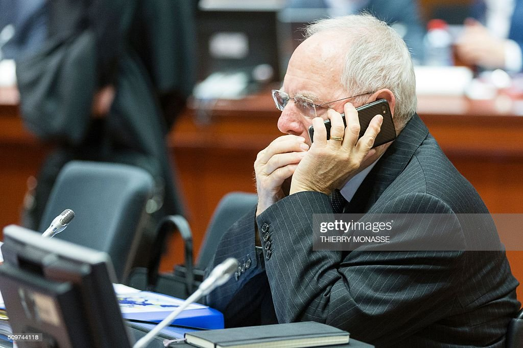 German Finance Minister Wolfgang Schaeuble speaks on his mobile phone prior to the start of the European Union Eco-Finance Council meeting at the EU Council building in Brussels on February 12, 2016. AFP PHOTO / THIERRY MONASSE / AFP / THIERRY MONASSE