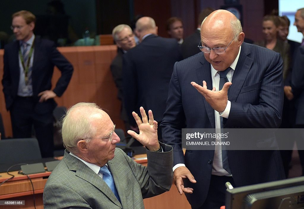 German Finance Minister Wolfgang Schauble and French Finance Minister Michel Sapin gesture as they attend an extraordinary Eurogroup meeting on...