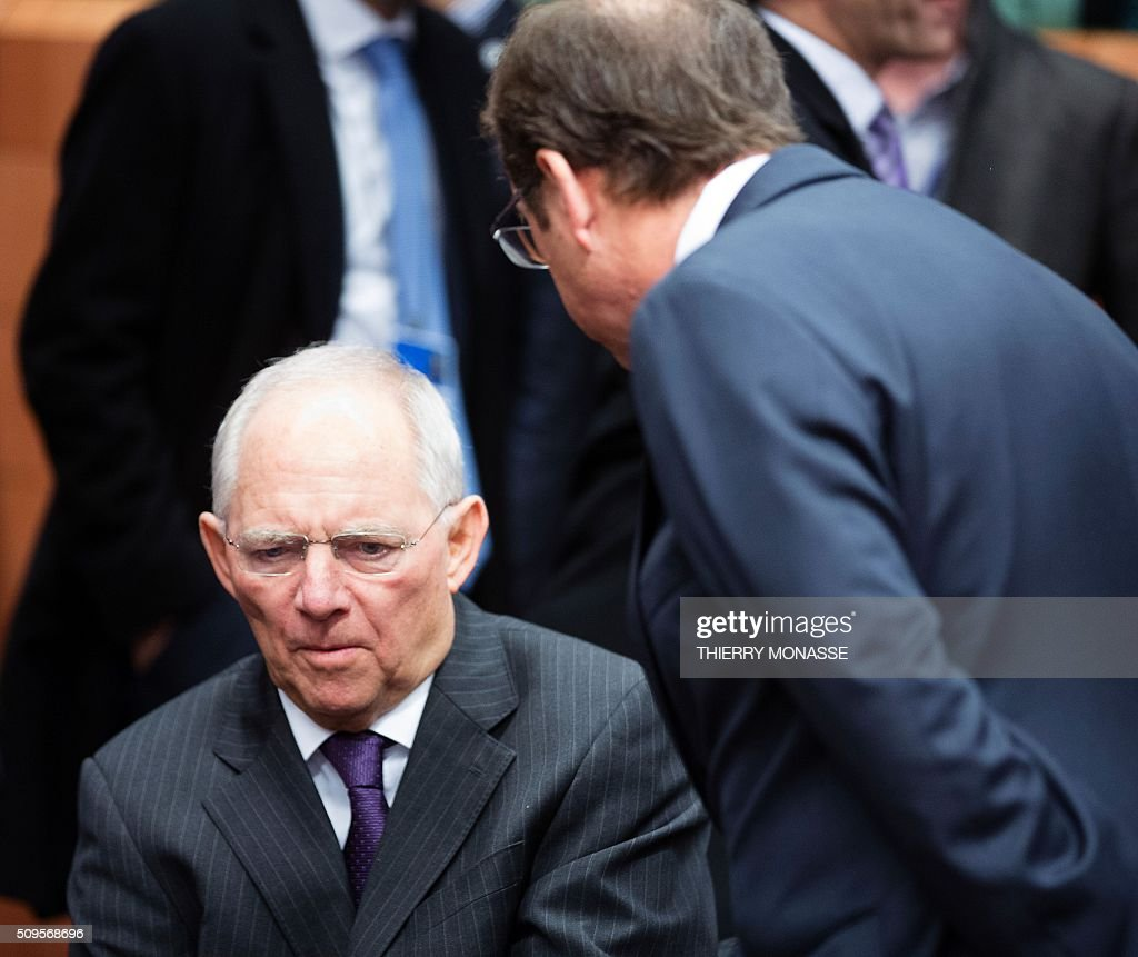 German Finance Minister Wolfgang Schauble (L) talks with the Slovenian Finance Minister Dusan Mramor (Back) prior to a meeting of Eurogroup ministers at the European Council headquarters in Brussels on February 11, 2016. / AFP / THIERRY MONASSE