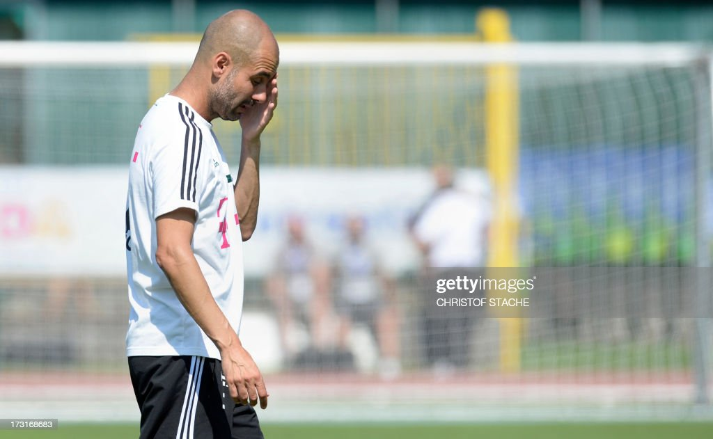 German first division Bundesliga football club FC Bayern Munich's Spanish head coach Pep Guardiola wipes his face during a training session at the team's summer training camp in Arco, Italy, on July 9, 2013. AFP PHOTO/CHRISTOF STACHE
