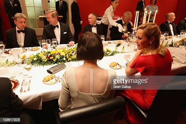 German First Lady Bettina Wulff chats with Swiss President Doris Leuthard as German President Christian Wulff chats with Mrs Leuthard's husband...