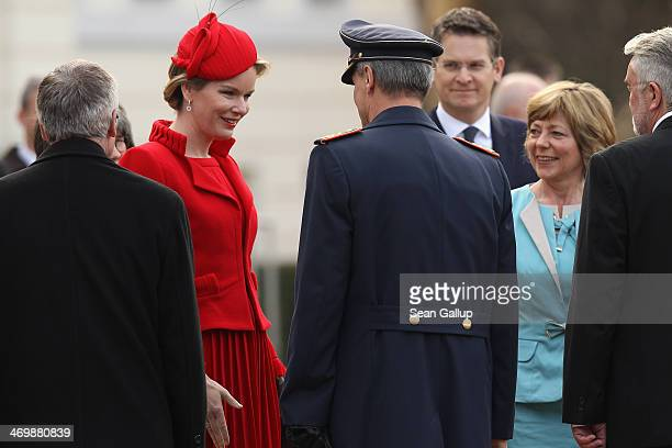 German First Lady Daniella Schadt and Queen Mathilde of Belgium greet members of the German presidential office outside Schloss Bellevue on February...