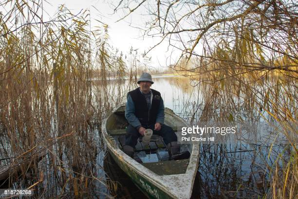 A German fisherman in his boat in Uckermarkische Seen Natural park part of the The Feldberg Lake District Nature Park containing large lakes kettle...