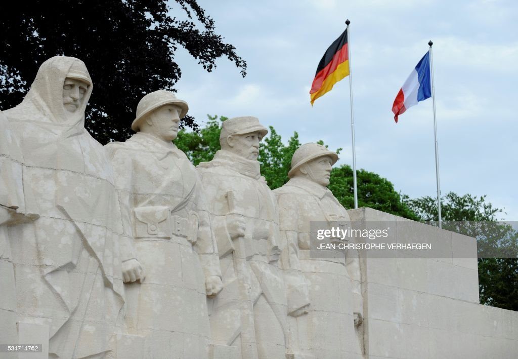 German flag and French flag are pictured in front of the War Memorial 1914-18, on May 27, 2016 in Verdun, eastern France. / AFP / JEAN