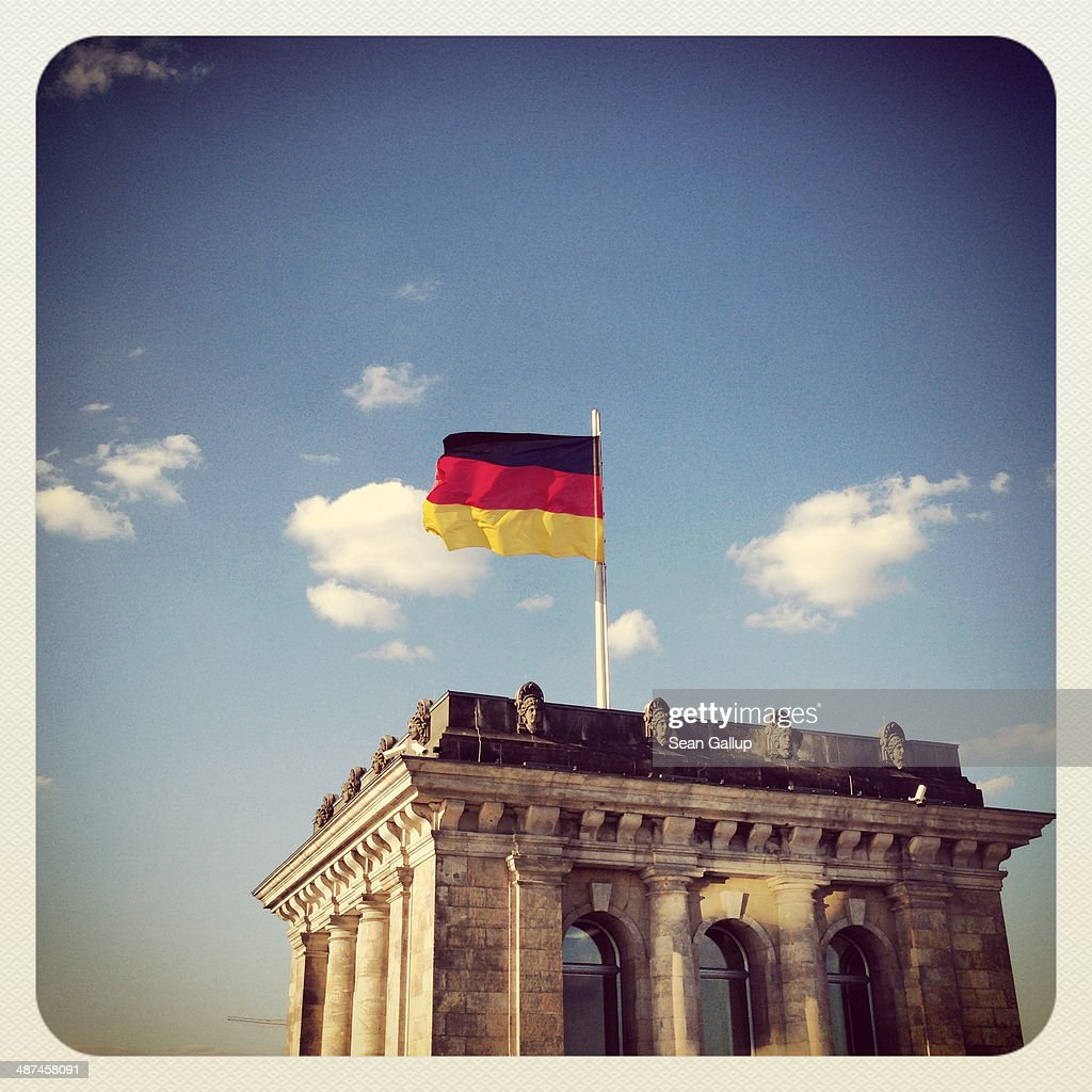 A German flag flies over a corner structure of the Reichstag on April 28, 2014 in Berlin, Germany. The Reichstag, home of the Bundestag, the German parliament, is among the city's major landmarks and a favourite tourist destination.