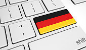 Digitalization and use of digital technologies in Germany with the German flag on a computer key.