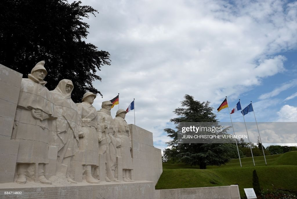 German flags and French flags are pictured in front of the War Memorial 1914-18, on May 27, 2016 in Verdun, eastern France. / AFP / JEAN