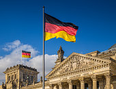 German flags waving in the wind at famous Reichstag building, seat of the German Parliament (Deutscher Bundestag), on a sunny day with blue sky and clouds, central Berlin Mitte district, Germany.