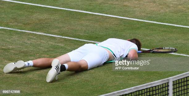 German Florian Mayer lies on the ground as he plays against French Lucas Pouille during the ATP tournament tennis match in Halle western Germany on...