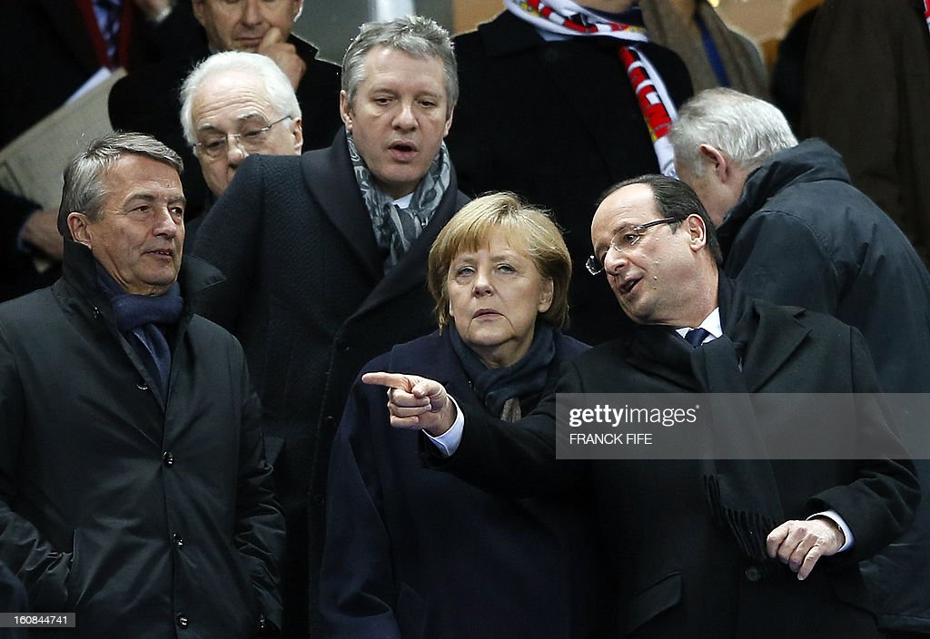 German Football Federation (DFB) president Wolfgang Niersbach, former presidential sports advisor Thierry Rey, German Chancellor Angela Merkel and France's President Francois Hollande attend a friendly international football match between France and Germany on February 6, 2013 at the Stade de France in Saint-Denis, near Paris.