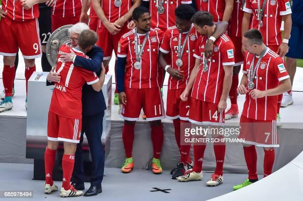German football league president Reinhard Rauball hugs Bayern Munich's German defender Philipp Lahm after his last match for the team after the...