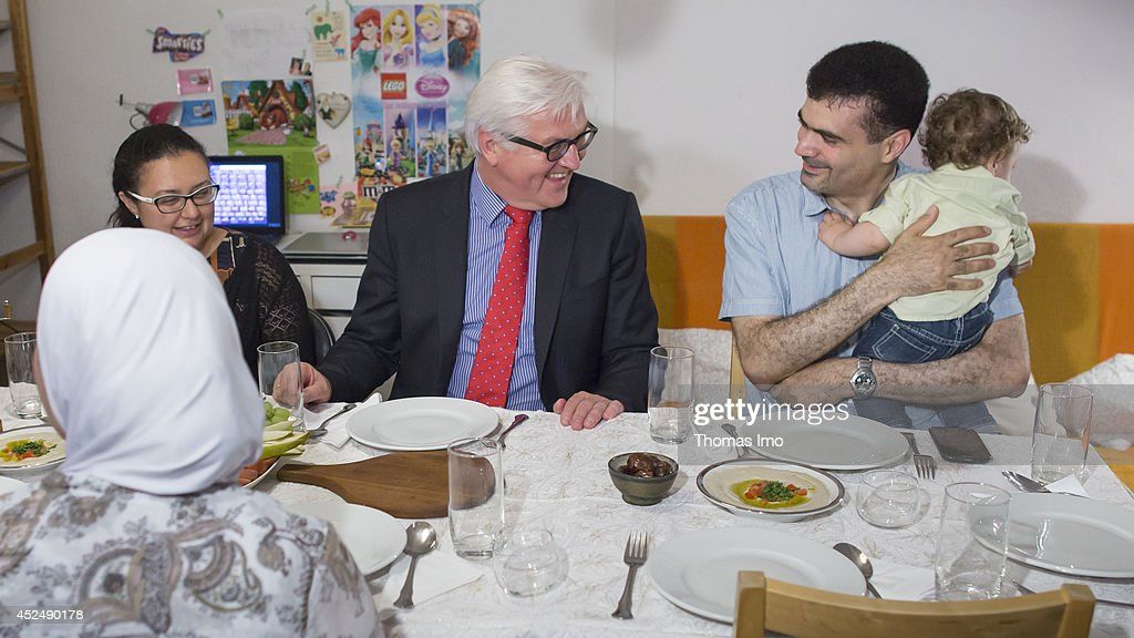 German Foreign Minister <a gi-track='captionPersonalityLinkClicked' href=/galleries/search?phrase=Frank-Walter+Steinmeier&family=editorial&specificpeople=603500 ng-click='$event.stopPropagation()'>Frank-Walter Steinmeier</a> and a syrian refugee family breaking their fast during the holy fasting month of Ramadan on July 21, 2014 in Berlin, Germany.