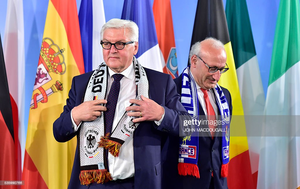 German Foreign Minister Frank-Walter Steinmeier (L) and French Ambassador to Germany Philippe Etienne wear their national football team's scarves during a function at the foreign ministry in Berlin on May 31, 2016, ahead of the UEFA Euro 2016 taking place in France next month. / AFP / John MACDOUGALL