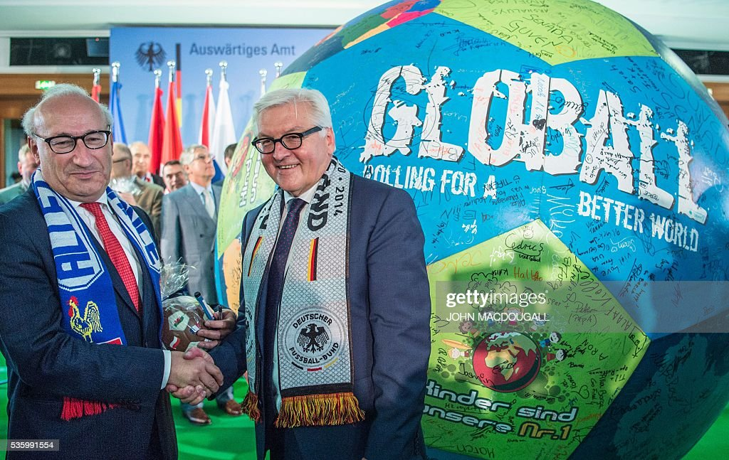 German Foreign Minister Frank-Walter Steinmeier (R) and French Ambassador to Germany Philippe Etienne shake hands after signing a giant football during a function at the foreign ministry in Berlin on May 31, 2016, ahead of the UEFA Euro 2016 taking place in France next month. / AFP / John MACDOUGALL