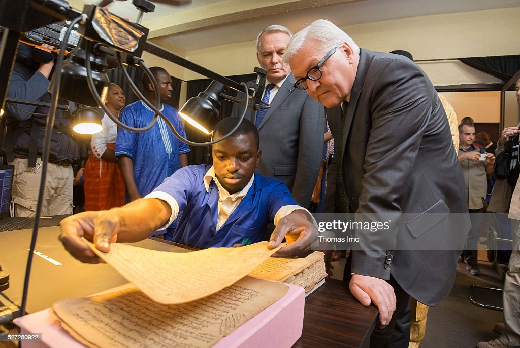 German Foreign Minister Frank-Walter Steinmeier (R) and French Foreign Minister Marc Ayrault (C) look at the historic scriptures of Timbuktu on May 02, 2016 in Bamako, Mali. Steinmeier and Ayrault visit Mali and Niger for political conversations.