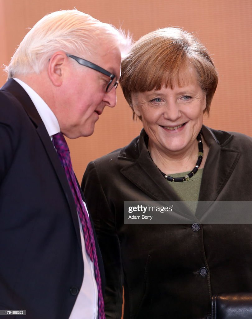 German Foreign Minister FrankWalter Steinmeier and German Chancellor Angela Merkel arrive for the weekly German federal Cabinet meeting on March 19...