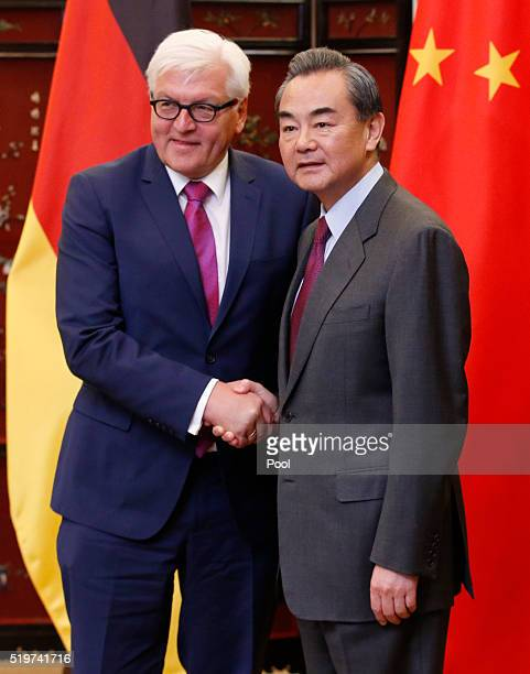 German Foreign Minister FrankWalter Steinmeier and his Chinese counterpart Wang Yi shake hands as they post for pictures during the second round of...
