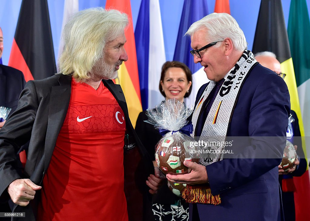 German Foreign Minister Frank-Walter Steinmeier (R) chats with Turkish Ambassador to Germany, Huseyin Avni Karslioglu (L) who is wearking Turkey's football jersey during a function at the foreign ministry in Berlin on May 31, 2016, ahead of the UEFA Euro 2016 taking place in France next month. / AFP / John MACDOUGALL