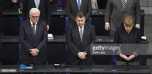 German Foreign Minister FrankWalter Steinmeier German Economy Minister Sigmar Gabriel and German Chancellor Angela Merkel stand during a minute's...