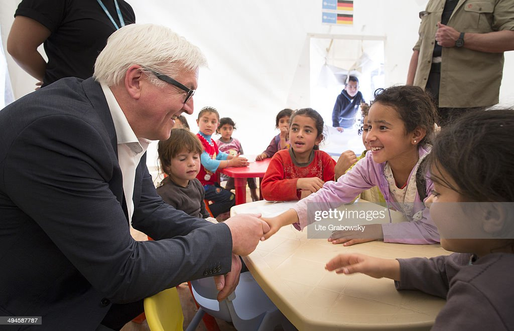 German Foreign Minister FrankWalter Steinmeier greets children during his visit to the refugee camp Barr Elias on May 30 2014 in Zahle Lebanon The...
