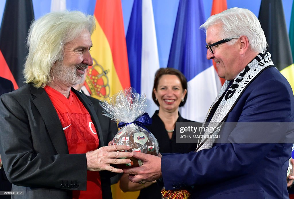 German Foreign Minister Frank-Walter Steinmeier (R) hands a chocolate football to Turkish Ambassador to Germany, Huseyin Avni Karslioglu (L) who is wearing Turkey's football jersey during a function at the foreign ministry in Berlin on May 31, 2016, ahead of the UEFA Euro 2016 taking place in France next month. / AFP / John MACDOUGALL