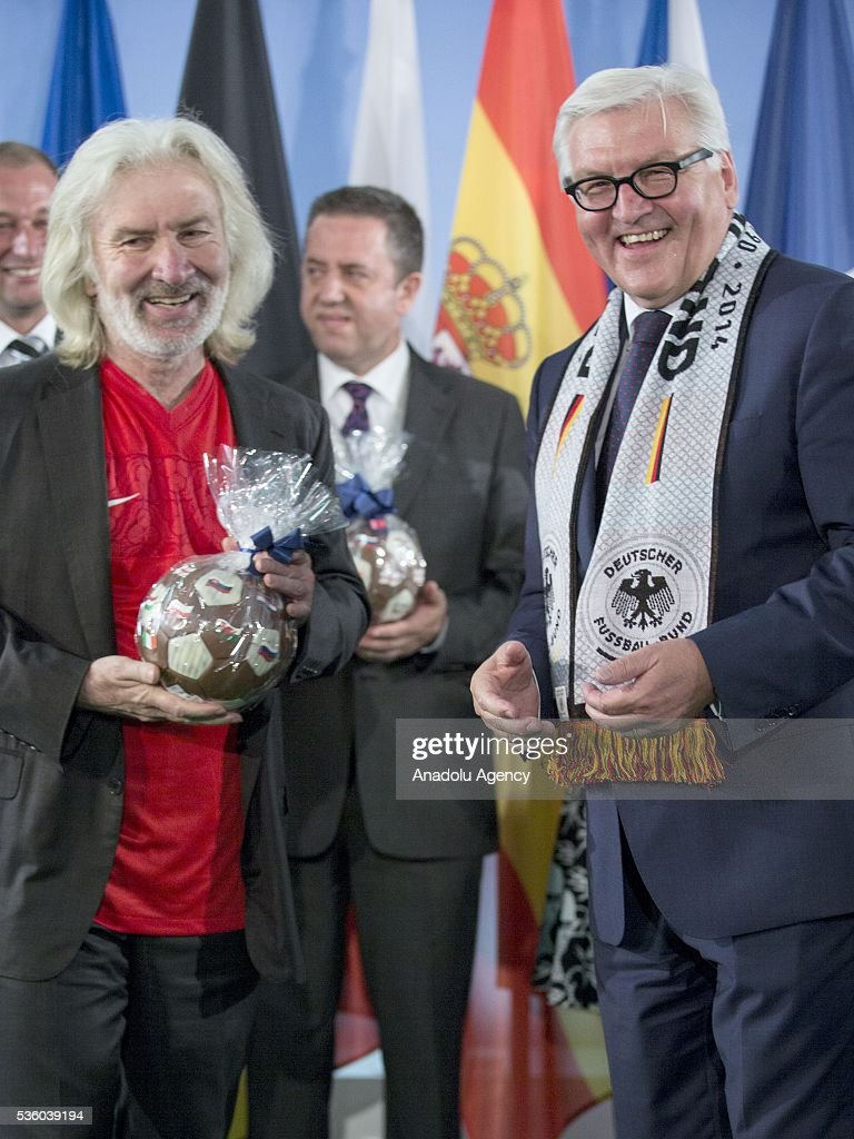 German Foreign Minister Frank-Walter Steinmeier (R) hands a chocolate football to Turkish Ambassador to Germany, Huseyin Avni Karslioglu (L) who is wearing Turkey's football jersey during a function at the foreign ministry in Berlin on May 31, 2016, ahead of the UEFA Euro 2016 taking place in France next month.