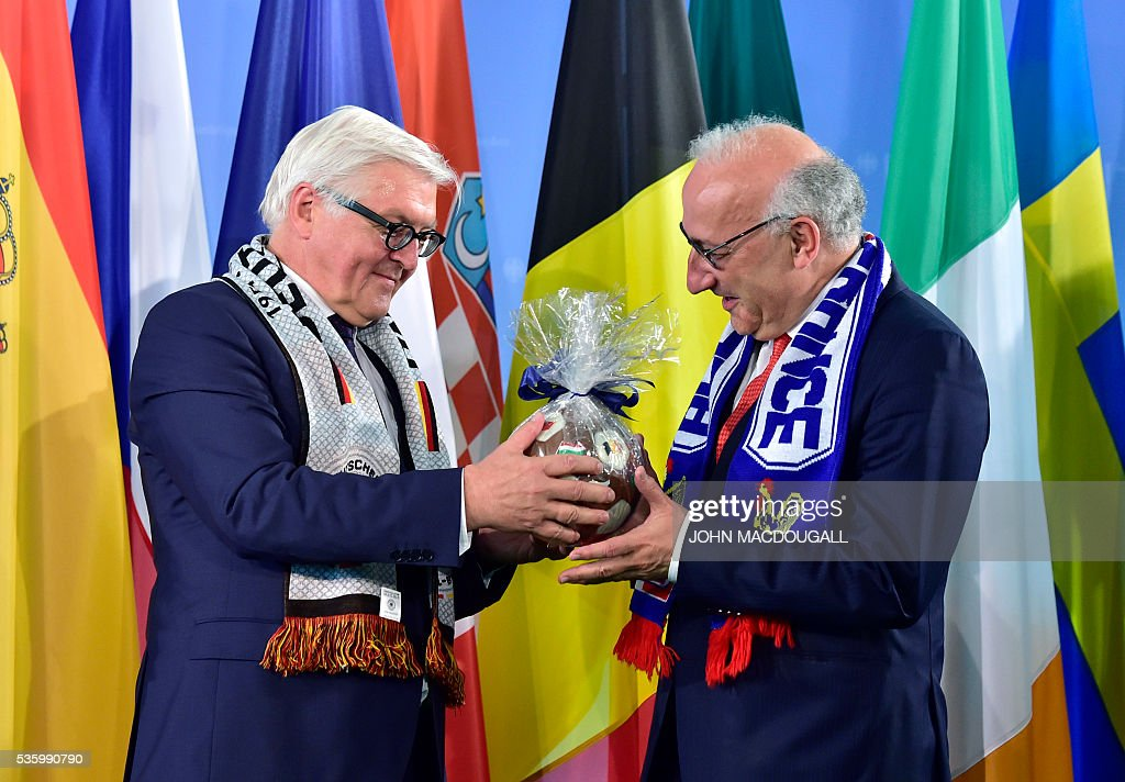 German Foreign Minister Frank-Walter Steinmeier (L) hands a football made of chocolate to French Ambassador to Germany Philippe Etienne during a function at the foreign ministry in Berlin on May 31, 2016, ahead of the UEFA Euro 2016 taking place in France next month. / AFP / John MACDOUGALL