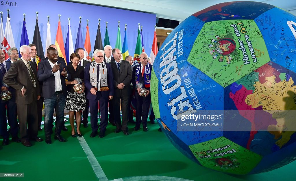 German Foreign Minister Frank-Walter Steinmeier (front row, 3rdR) looks on as a helper pushes a giant football across the floor for guests to sign during a function at the foreign ministry in Berlin on May 31, 2016, ahead of the UEFA Euro 2016 taking place in France next month. / AFP / John MACDOUGALL