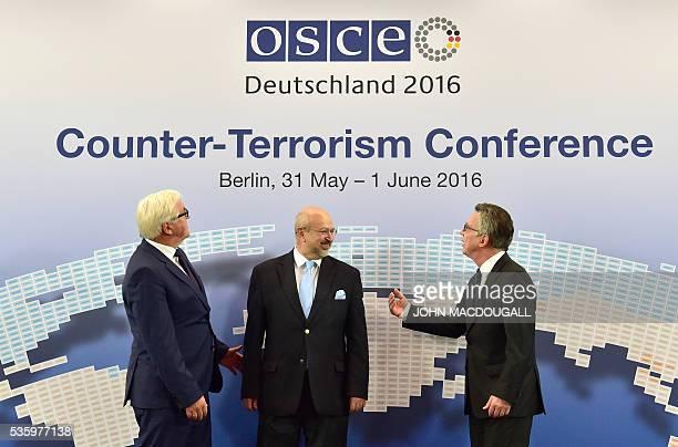 German Foreign Minister FrankWalter Steinmeier OSCE Secretary General Lamberto Zannier and German Interior Minister Thomas de Maiziere pose for...