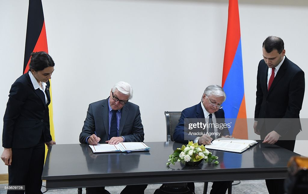 German Foreign Minister Frank-Walter Steinmeier, who currently chairs the Organisation for Security and Cooperation in Europe (OSCE) (C-L) and Armenian Foreign Minister Edward Nalbandian (C-R) sign an agreement on double taxation in Yerevan on June 29, 2016