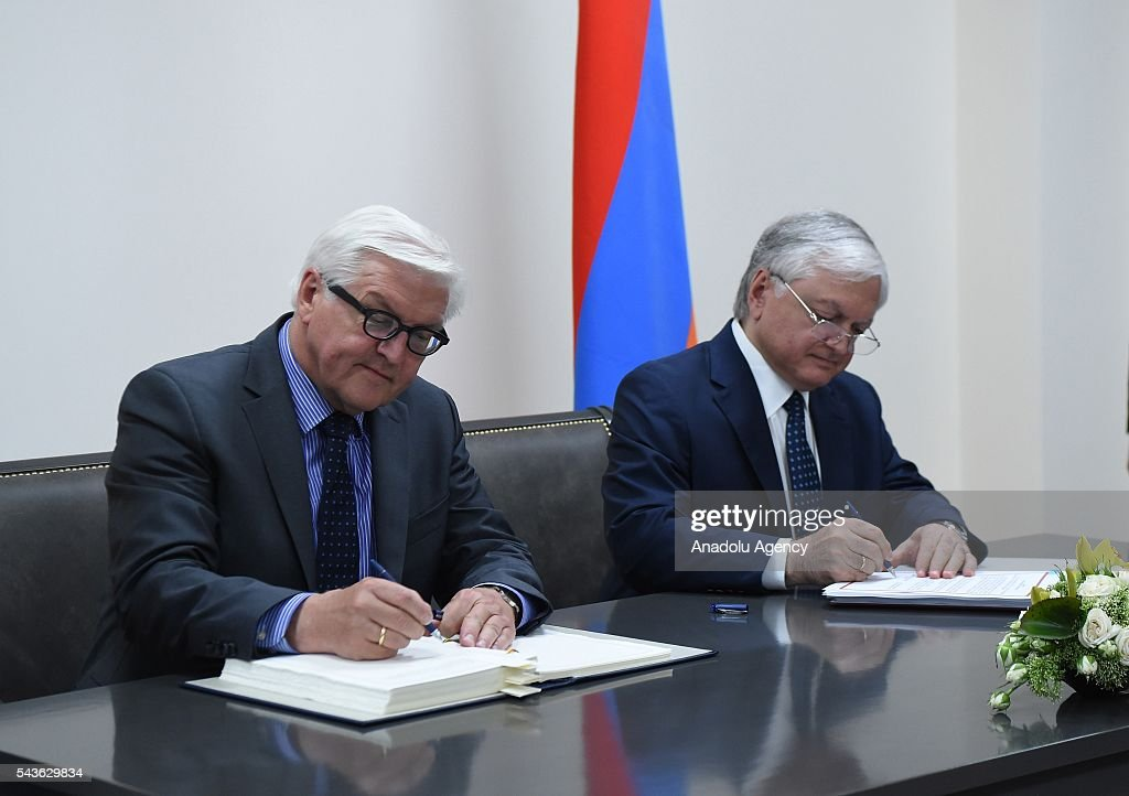 German Foreign Minister Frank-Walter Steinmeier, who currently chairs the Organisation for Security and Cooperation in Europe (OSCE) (L) and Armenian Foreign Minister Edward Nalbandian (R) sign an agreement on double taxation in Yerevan on June 29, 2016