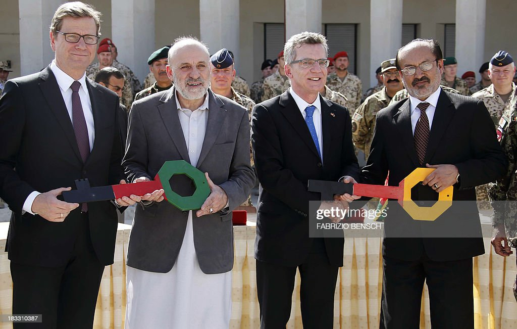 German Foreign Minister Guido Westerwelle (L), Afghan Interior Minister Mohammad Omar Daudzai (2nd L), German Defence Minister Thomas de Maiziere (2nd R) and Afghanistan's Deputy Defence Minister Enayatullah Nazari exchange symbolic keys during the handover ceremony of a German base to Afghan armed forces in Kunduz, Afghanistan on October 6, 2013. Soldiers of the German contingency of the International Security Assistance Force (ISAF) withdrew from their base in Kunduz and the camp will be used by the Afghan National Army (ANA) and the Afghan National Civil Order Police (ANCOP).