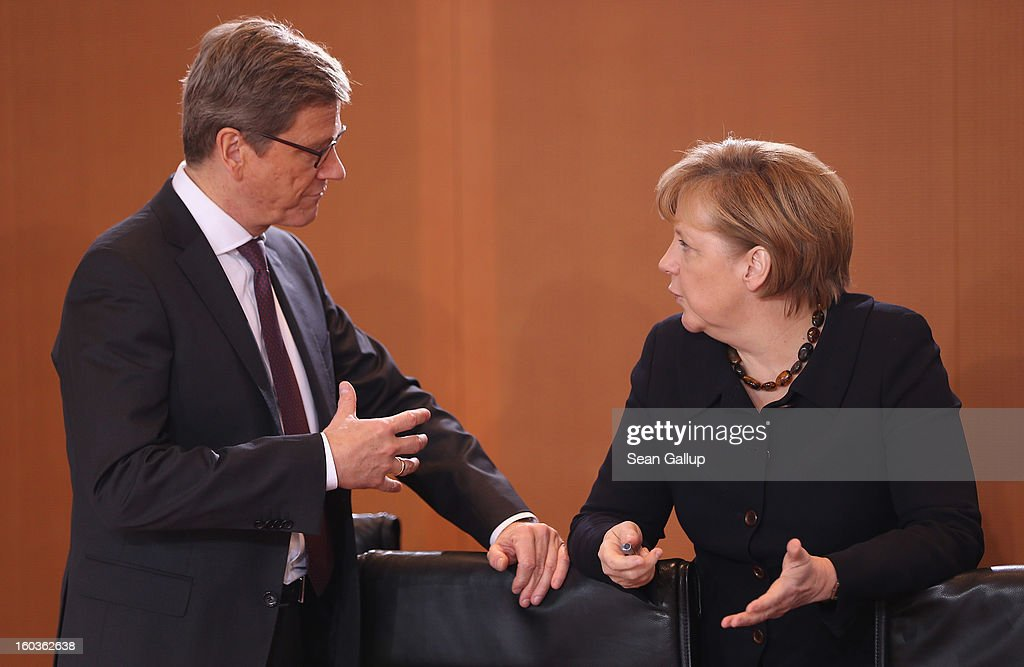German Foreign Minister <a gi-track='captionPersonalityLinkClicked' href=/galleries/search?phrase=Guido+Westerwelle&family=editorial&specificpeople=208748 ng-click='$event.stopPropagation()'>Guido Westerwelle</a> and Chancellor Angela Merkel chat prior to the weekly German government cabinet meeting on January 30, 2013 in Berlin, Germany. High on the morning's agenda was a measure that will affect Germany's state railway network.