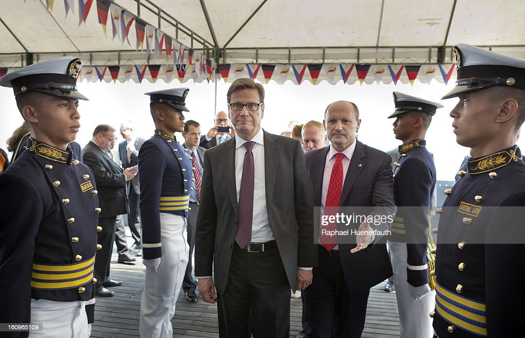 German Foreign Minister Guido Westerwelle (L) and Cliff Davies (R), Praesident Doehle Philippines, with cadets of the Philippin Merchant Marine Academy 'Elite' on the roof of the Doehle Haus on February 8, 2013 in Manila, Philippines. Westerwelle, who is the first German Foreign Minister to visit the Philippines in more than twelve years, is in Manila to discuss bilateral trade and relations accompanied by a 12-man business delegation.